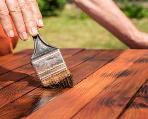 Bild zeigt Handwerker beim Lackieren von Gartenmöbeln